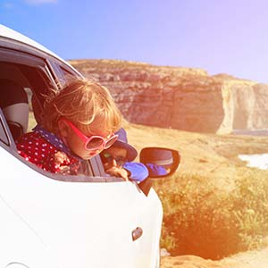 A little girl with oversized sunglasses peers out the window of the car as they drive on the coastline.