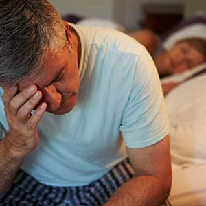 A man suffering from chronic insomnia sits on the edge of his bed, rubbing his head while his wife sleeps behind him.