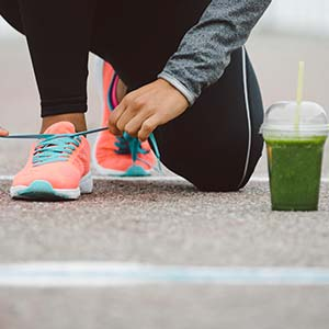 An athletic woman ties her shoelaces outside with a green juice propped next to her.