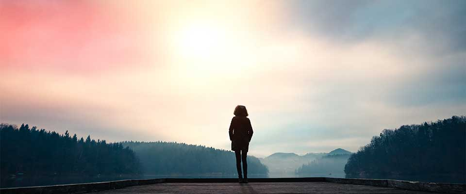 A woman stands at the edge of a serene lake. She is silhouetted by the sun. She keeps her hands in her pockets as she practices mindfulness meditation.