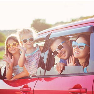 A young, smiling family wearing sunglasses to prevent sun damage to eyes waves from their car.