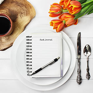 A pen and journal sit on a fancy white table between a set of silverware and a cup of coffee.