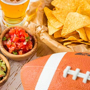 Chips, salsa, beer, and a football sit on a wooden table.