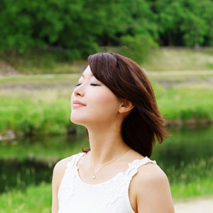 A girl with black hair practices deep breathing in the middle of a field.