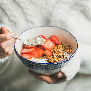 A woman in a white sweater spoons granola, yogurt, and strawberries from a bowl.