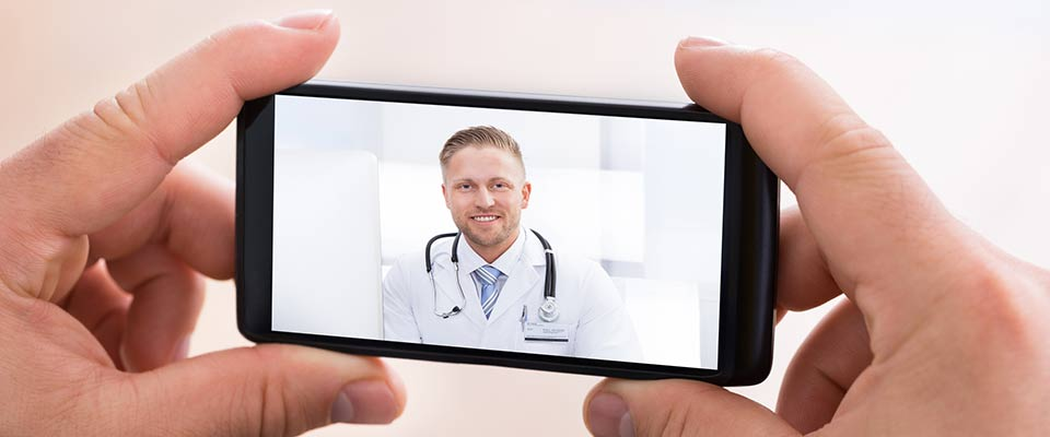 During a telehealth session, a pair of hands holds a phone displaying video of a smiling doctor in a white coat.