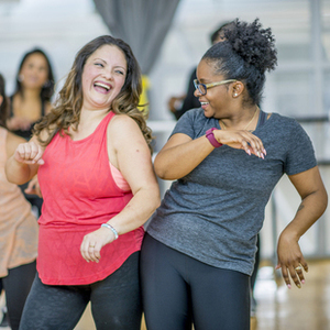 A group of women in a fitness studio are pictured exercising together and having fun.